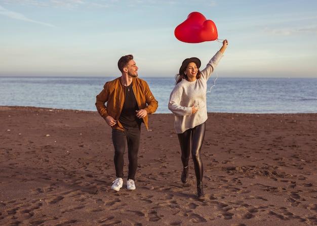 Casal feliz correndo na beira-mar com balões de coração Foto gratuita