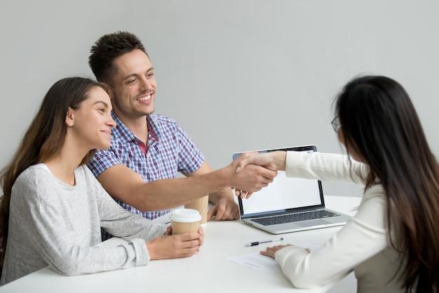 Casal feliz cumprimentando consultor financeiro Foto gratuita