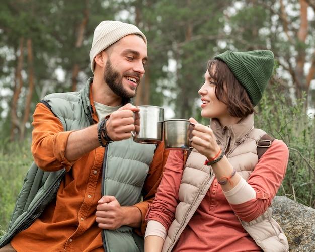 Casal feliz curtindo uma bebida quente na natureza Foto gratuita