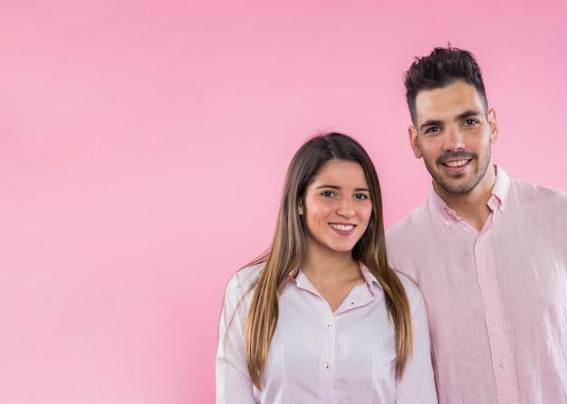 Casal feliz dançando no fundo rosa Foto gratuita