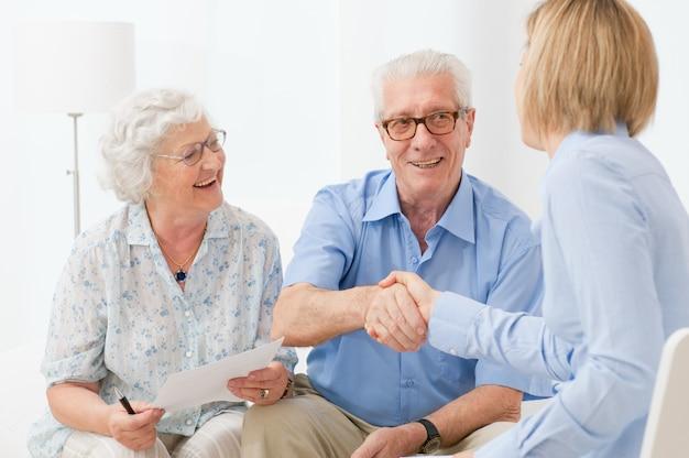 Casal feliz de idosos fechando um contrato de aposentadoria com um aperto de mão Foto Premium