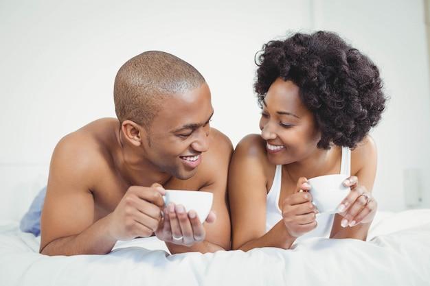 Casal feliz deitada na cama, segurando copos e falando Foto Premium