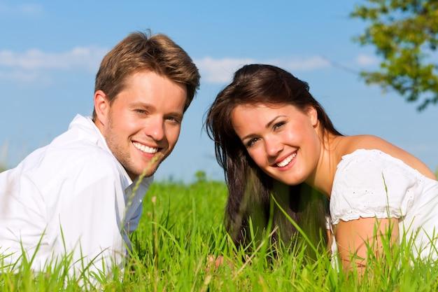 Casal feliz, deitado na grama em um campo ensolarado Foto Premium