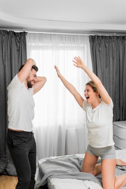 Casal feliz dentro de casa jogando juntos Foto gratuita