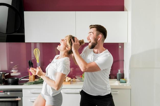 Casal feliz dentro de casa vista frontal Foto gratuita