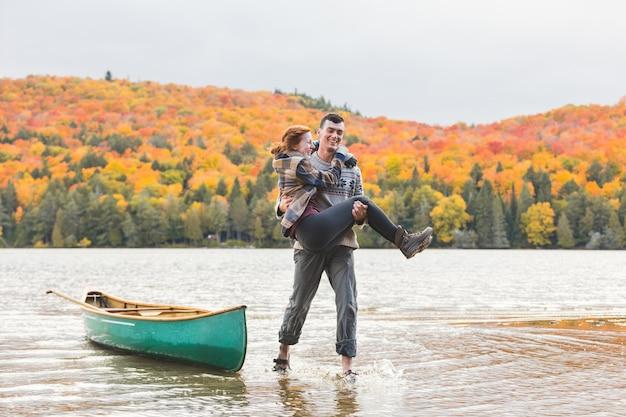 Casal feliz depois da viagem de canoa no lago no canadá Foto Premium