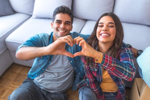 Casal feliz durante a mudança de casa mostrando sinal de coração Foto Premium