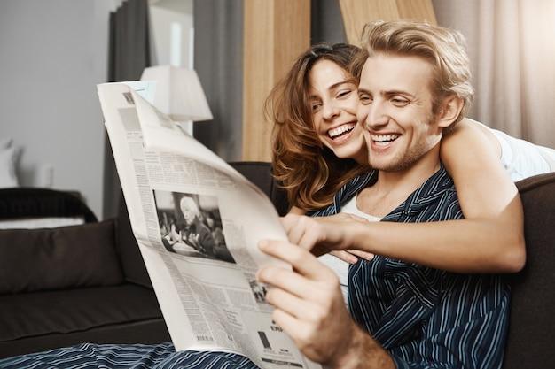 Casal feliz e atraente, apaixonado, lendo jornal em casa Foto gratuita