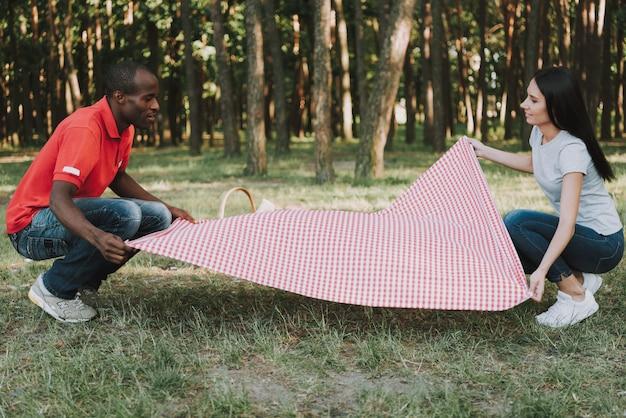Casal feliz espalhar toalha de mesa para piquenique. Foto Premium