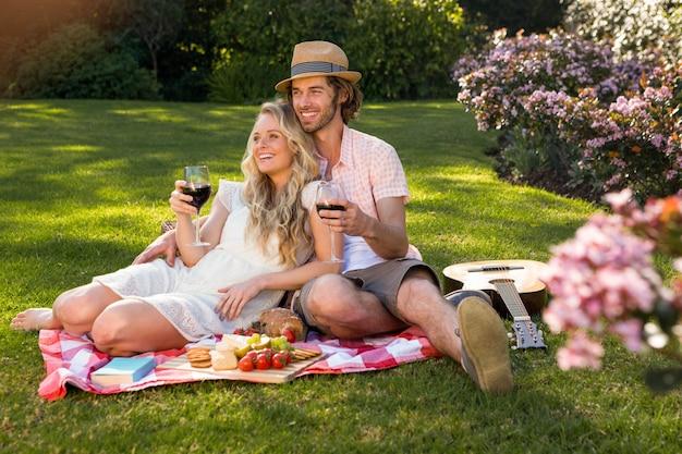 Casal feliz fazendo um piquenique e abraçando no jardim Foto Premium