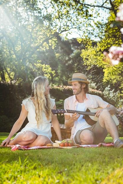 Casal feliz fazendo um piquenique e tocando violão no jardim Foto Premium