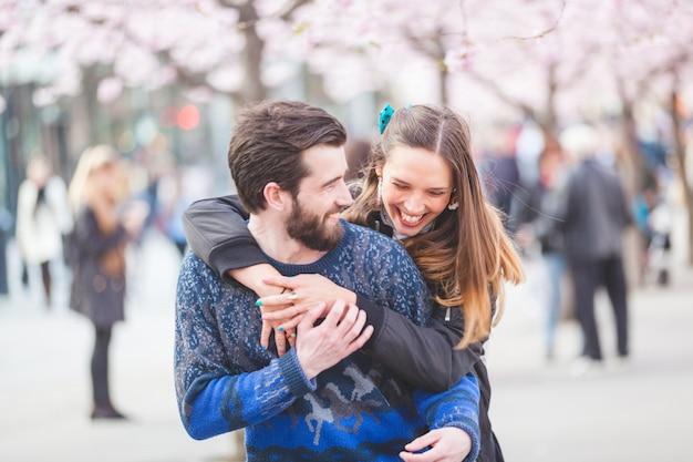Casal feliz hipster em estocolmo com flores de cerejeira Foto Premium