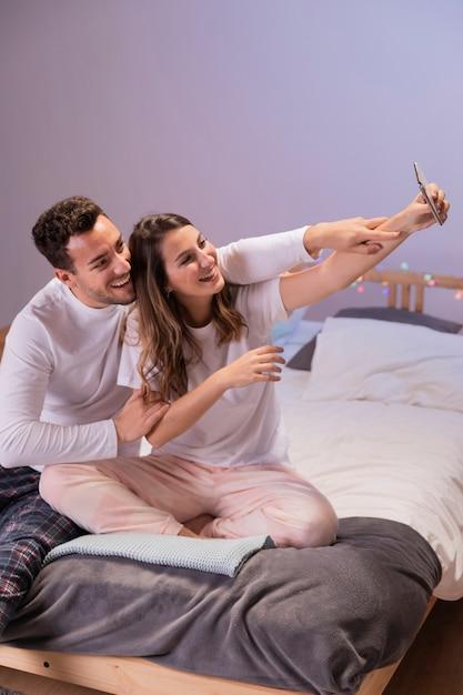 Casal feliz na cama tomando selfie Foto gratuita