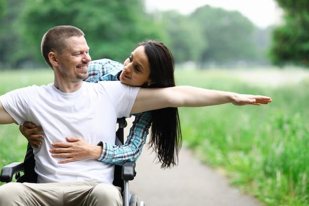 Casal feliz na caminhada no parque de cadeira de rodas com deficiência Foto Premium