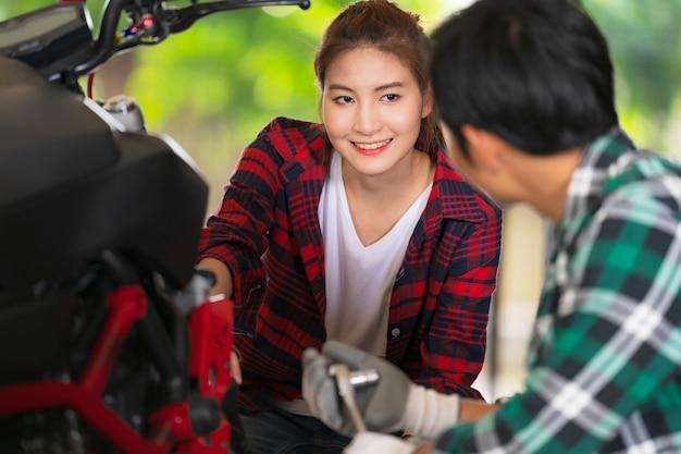 Casal feliz na oficina de reparação e motocicletas personalizadas Foto Premium