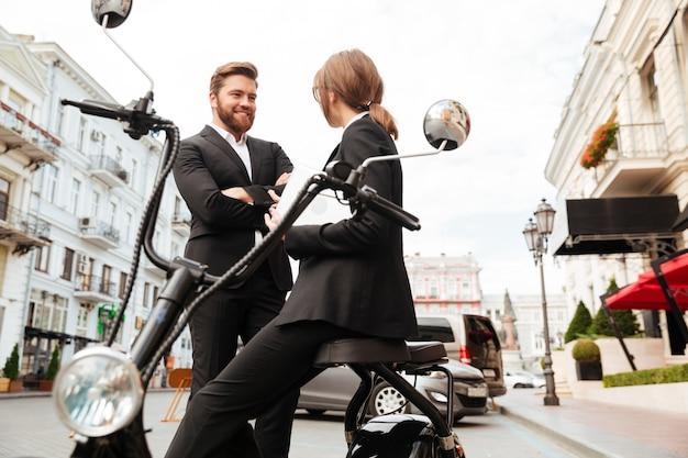 Casal feliz negócios posando perto da moto moderna ao ar livre Foto gratuita
