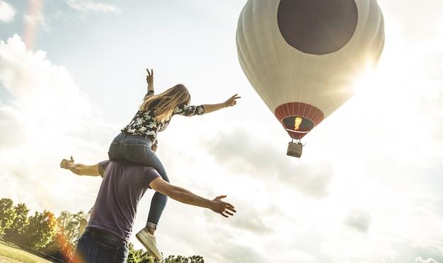Casal feliz no amor em férias de lua de mel, aplaudindo em balão de ar quente Foto Premium
