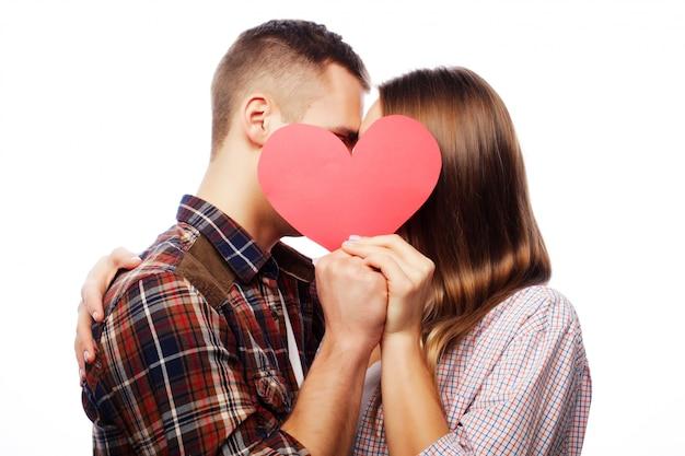 Casal feliz no amor segurando coração vermelho. Foto Premium