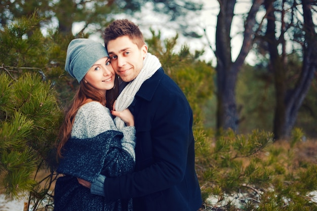 Casal feliz no chapéu morno e lenço abraçando ao ar livre no inverno Foto gratuita