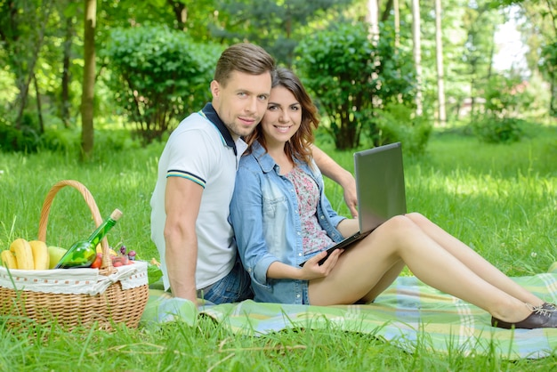 Casal feliz no piquenique com o laptop no parque. Foto Premium