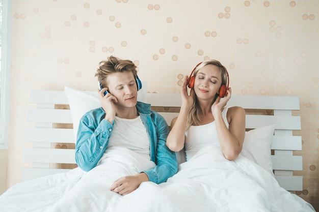 Casal feliz ouvindo música da manhã no quarto Foto gratuita