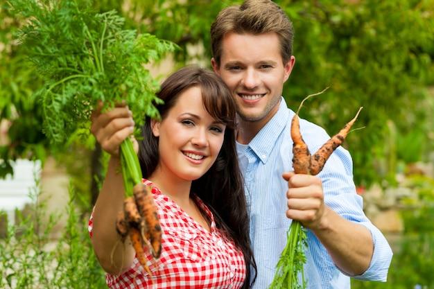 Casal feliz posando com as cenouras que acabaram de colher Foto Premium