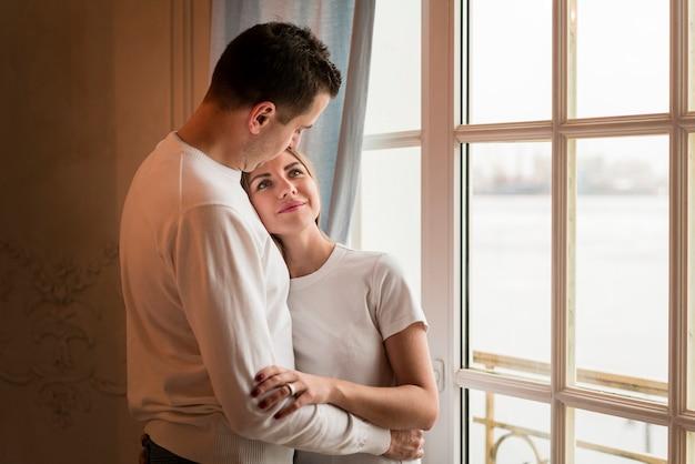 Casal feliz romântico abraçado ao lado da janela Foto gratuita
