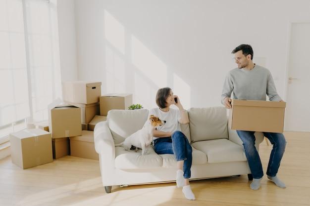 Casal feliz se move na nova casa, posar no sofá com animal de estimação e caixas Foto Premium