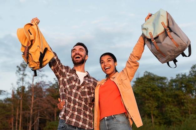 Casal feliz segurando as costas para cima Foto gratuita