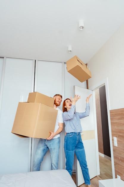 Casal feliz segurando caixas de papelão e movendo-se para novo lugar Foto gratuita