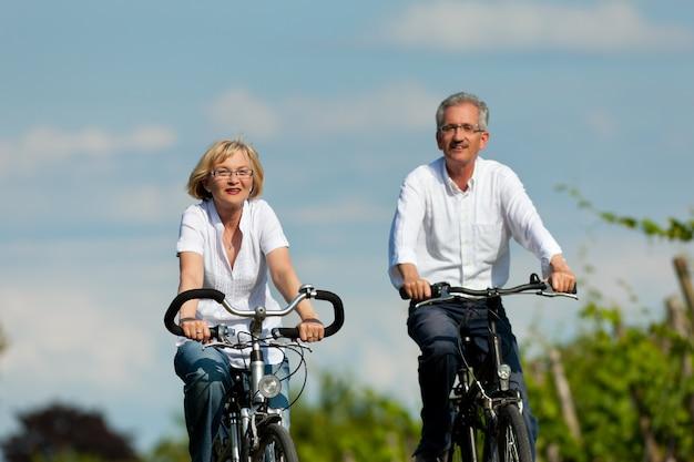 Casal feliz sênior, andar de bicicleta ao ar livre no verão Foto Premium