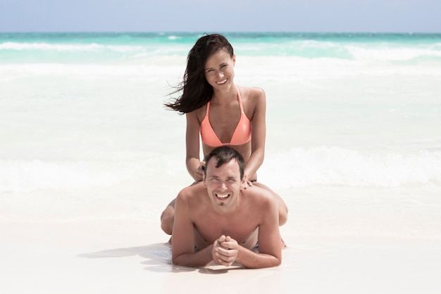 Casal feliz sentado na praia Foto gratuita