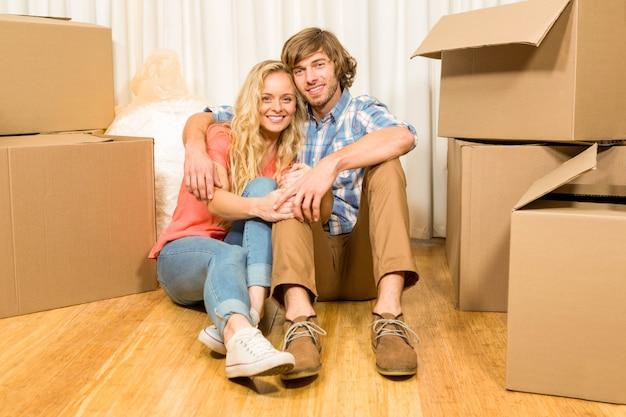 Casal feliz sentado no chão em casa nova Foto Premium