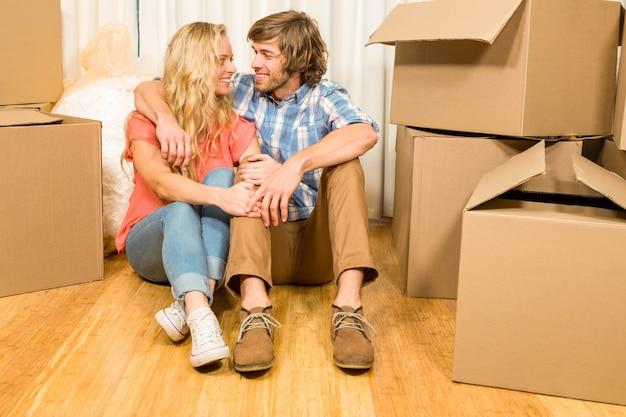 Casal feliz sentado no chão em sua nova casa Foto Premium