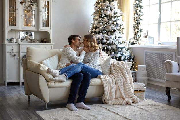 Casal feliz sentado no sofá em casa Foto Premium