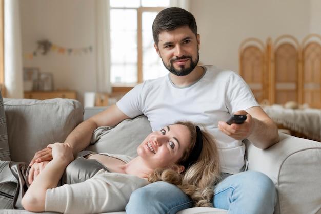 Casal feliz sentados juntos no sofá Foto gratuita