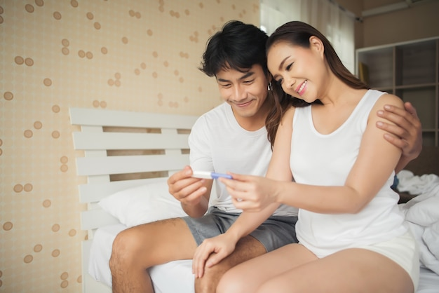 Casal feliz sorrindo depois de descobrir teste de gravidez positivo no quarto Foto gratuita