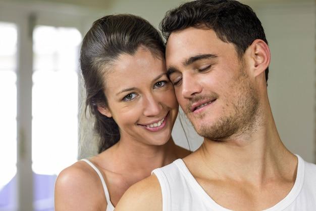 Casal feliz sorrindo para a câmera na cozinha Foto Premium