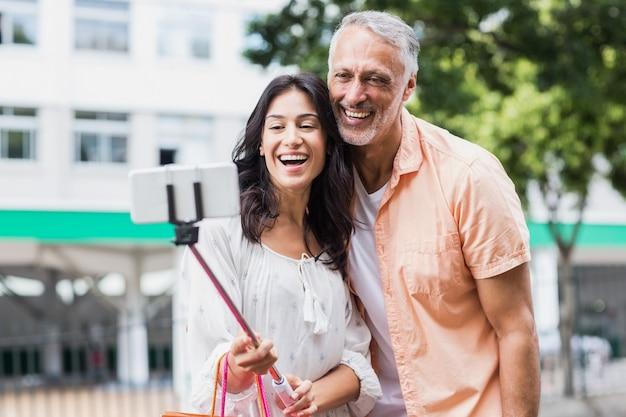 Casal feliz tendo selfie no monopé Foto Premium