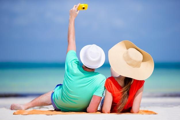 Casal feliz tirando uma foto auto em uma praia nos feriados Foto Premium