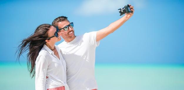 Casal feliz, tirando uma foto de selfie na praia branca. dois adultos curtindo suas férias na praia exótica tropical Foto Premium
