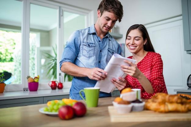Casal feliz tomando café da manhã e lendo jornal em casa Foto Premium