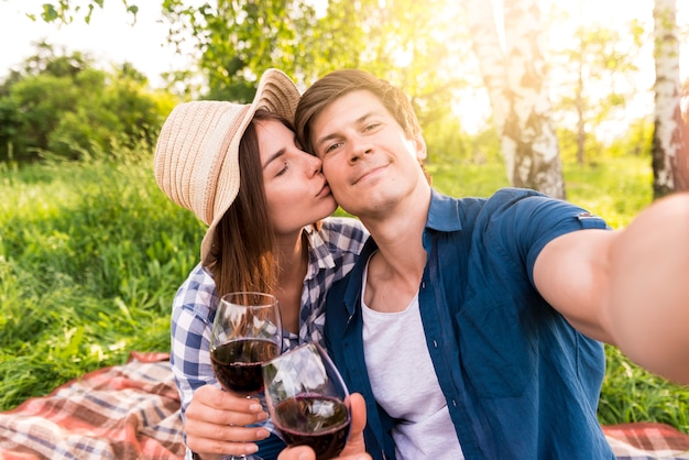 Casal feliz tomando selfie no piquenique Foto gratuita