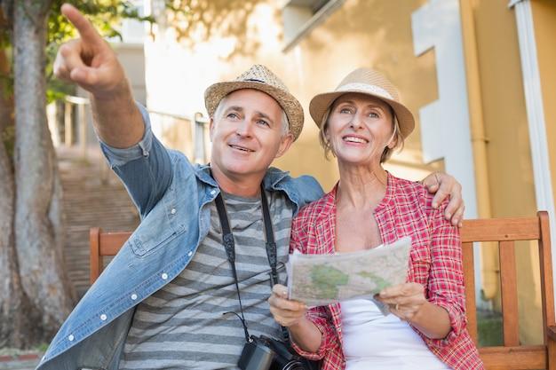 Casal feliz turista olhando o mapa em um banco na cidade Foto Premium