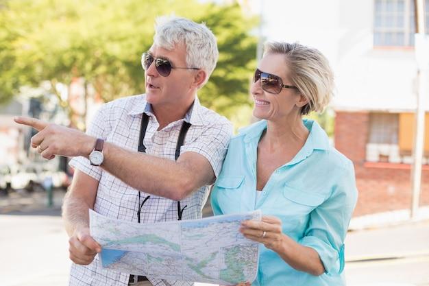 Casal feliz turista usando mapa da cidade Foto Premium