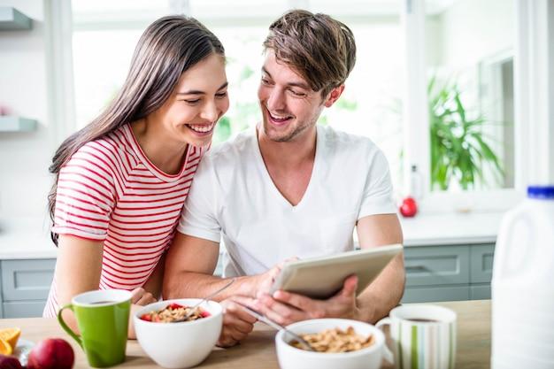 Casal feliz usando tablet e tomando café da manhã na cozinha Foto Premium