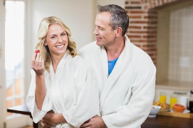 Casal fofo carinhos em roupões na cozinha Foto Premium
