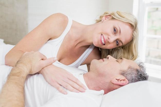 Casal fofo carinhos na cama no quarto deles Foto Premium
