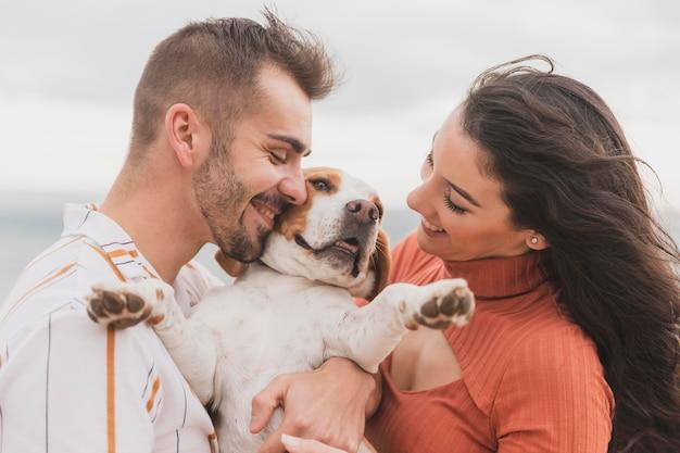 Casal fofo com cachorro na beira-mar Foto Premium