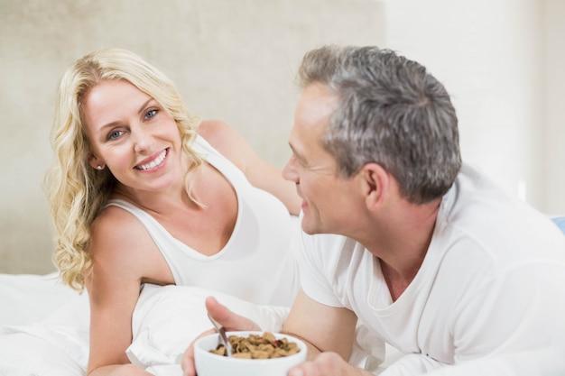 Casal fofo com uma tigela de cereais em sua cama Foto Premium